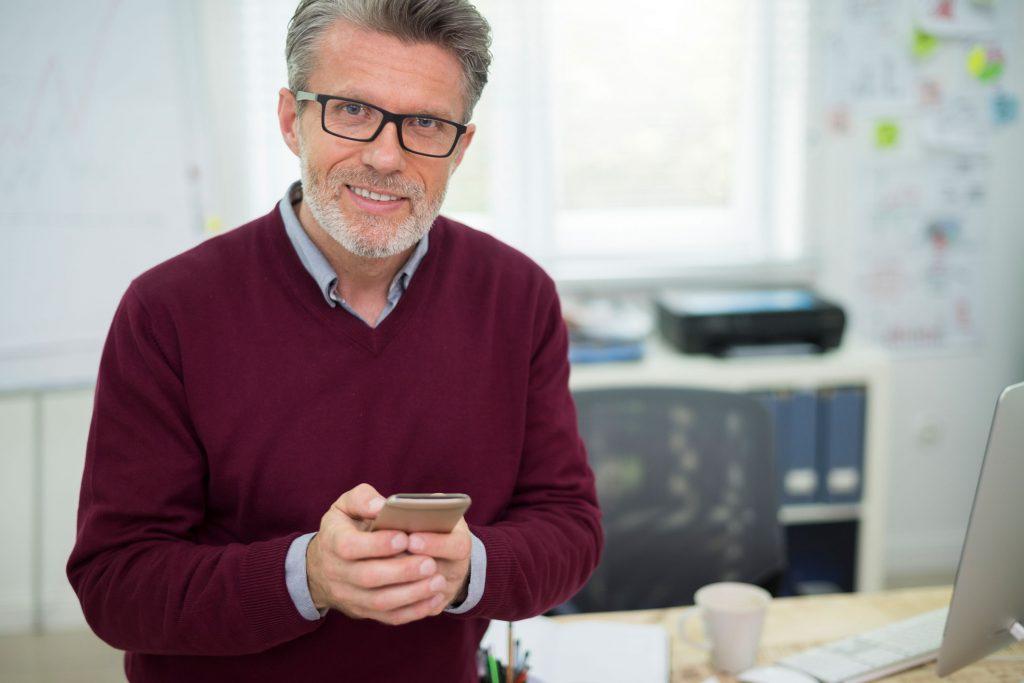 Empresário usando celular para aprovar pedido no GConsole